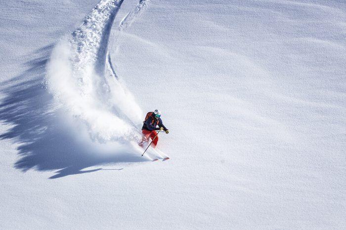 Free ride skier skiing down through fresh powder