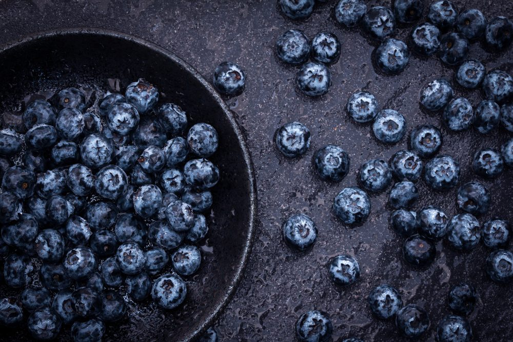fresh picked blueberries on black stone background