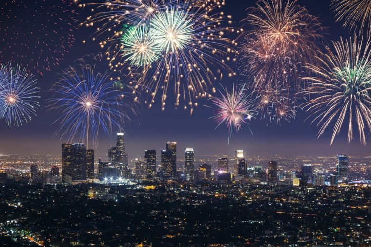 Downtown Los angeles cityscape with flashing fireworks celebrating New Year's Eve.