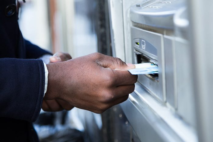 Close up of man taking cash from ATM with credit card.