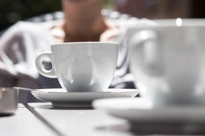 detail shot of white coffee cups on a grey wooden table outdoors