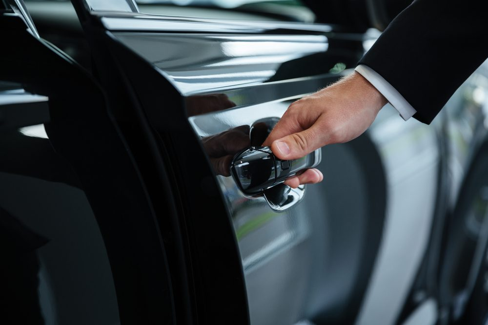 Close up of a male hand closing a car door at the dealership