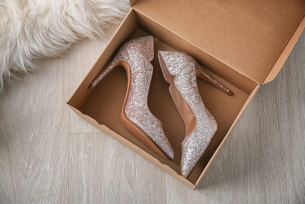 Box with pair of sparkly female shoes on floor, top view