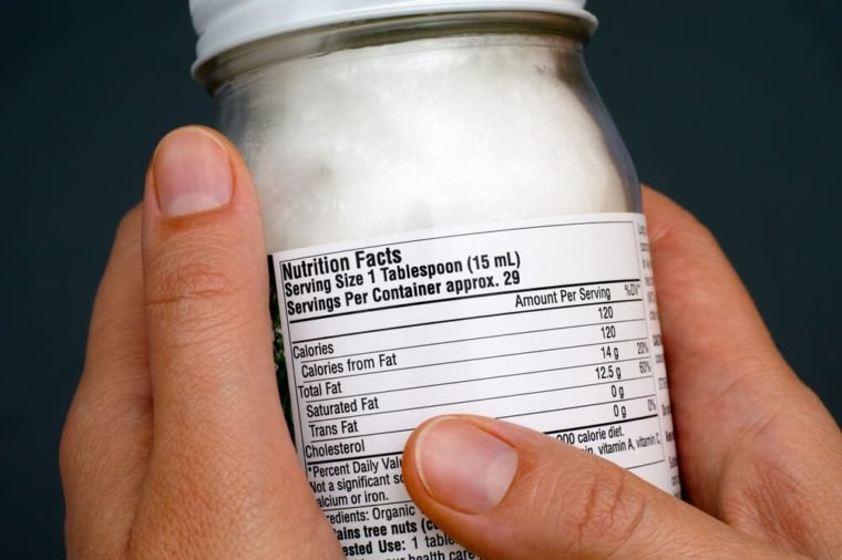 Reading a nutrition facts on organic coconut oil jar. Close-up.
