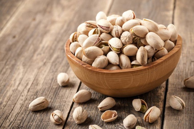 Pistachio nuts in a wooden bowl on wooden table