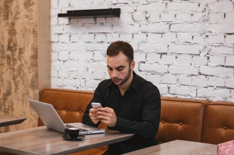 Shot of a young businessman working on his laptop and mobile in a cafe shop.