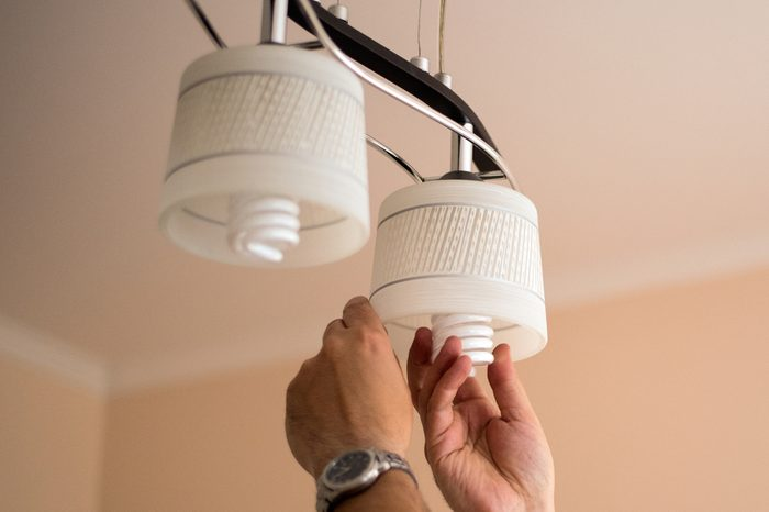 Man changes an electric light bulb, energy efficiency. Closeup of man's hand adjusting electric bulb by pendant lights at home.energy efficiency,. LED lamp