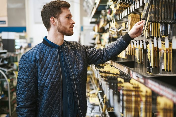 Bearded young man in a hardware store standing reading the information on a product hanging on the rack, side view close up