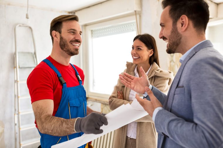Young smiling couple and handyman talking about details of renovations home