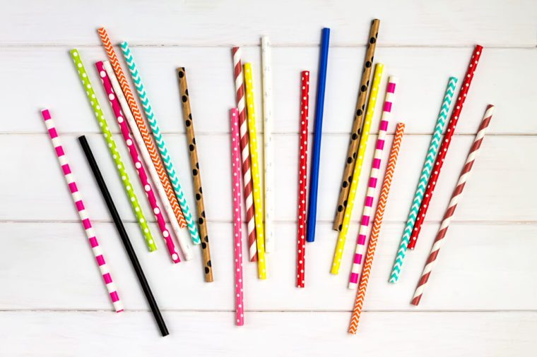 Colorful paper straws on white wooden background. Event and party supplies.
