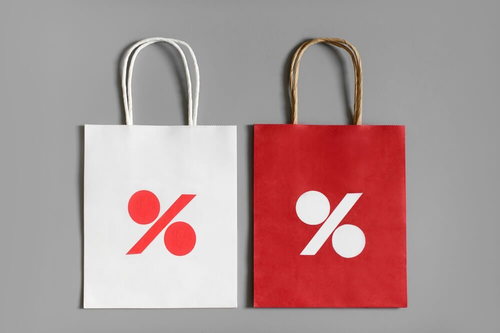 Red and white shopping bags from recycle paper with percent sign on gray background. Black friday or Christmas sales.