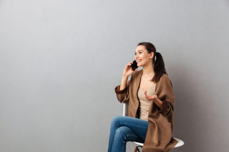 Portrait of a smiling casual asian woman talking on mobile phone while sitting on a chair over gray background