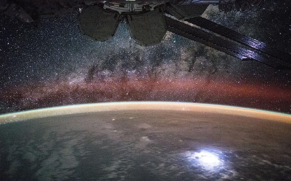 View (part of a time lapse sequence) of stars in the Milky Way Galaxy visible over an Earth limb as seen by the Expedition 44 crew. Astronaut Kjell Lindgren captured a lightning strike from space so bright that it lights up the space station's solar panels. He posted this on Twitter and Instagram on Sept. 2 saying