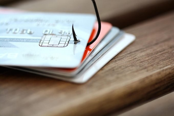 Credit card phishing scam with credit card in fishing hook on wooden table