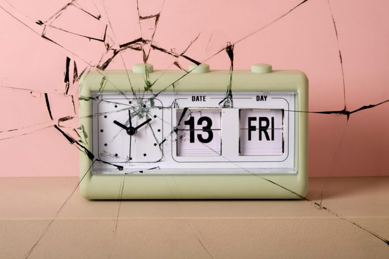 vintage clock with date that reads Fri 13. cracked texture overlay