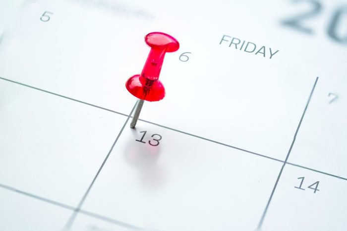 Red push pin on calendar friday the 13th day of the month