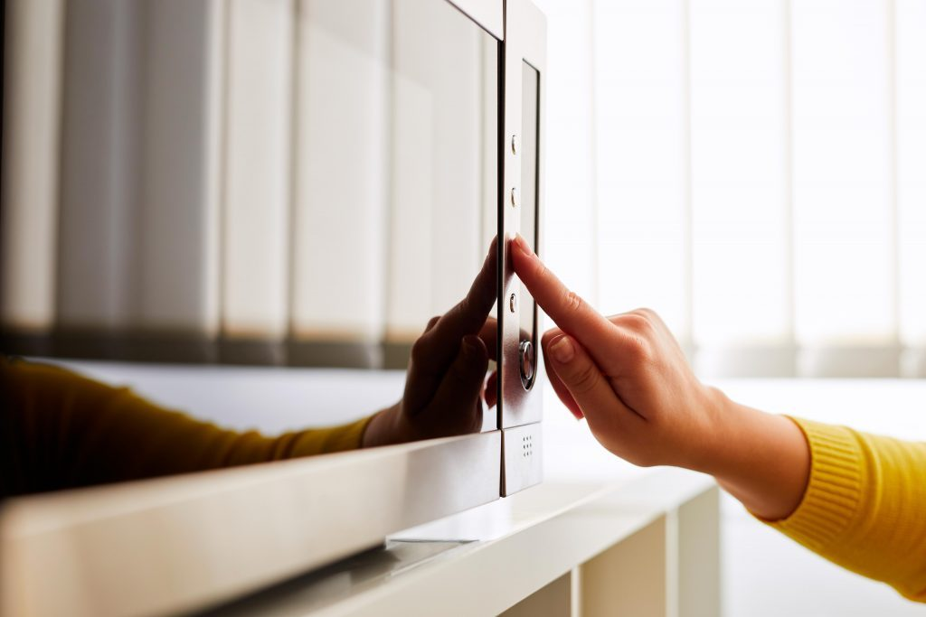 hand touching buttons on a microwave at home