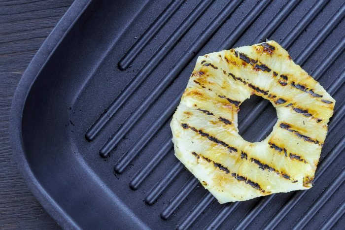 Fried pineapple on the grill. Cooking fish burger.