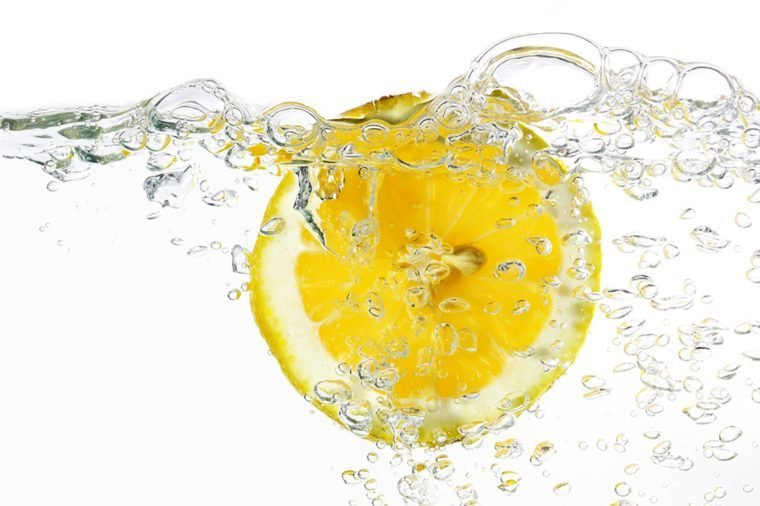 slice of lemon in water isolated light grey