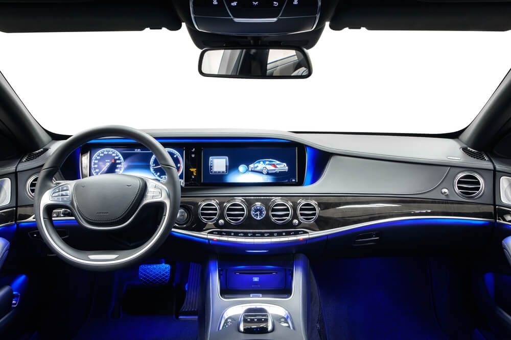 Car inside driver place. Interior of prestige modern car. Steering wheel, dashboard, display & climate control. Black cockpit with wood & metal decoration & ambient light on isolated white background.