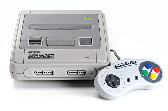 A Super Nintendo Entertainment System Video Game Console And Competition Pro Controller Photographed On A White Background