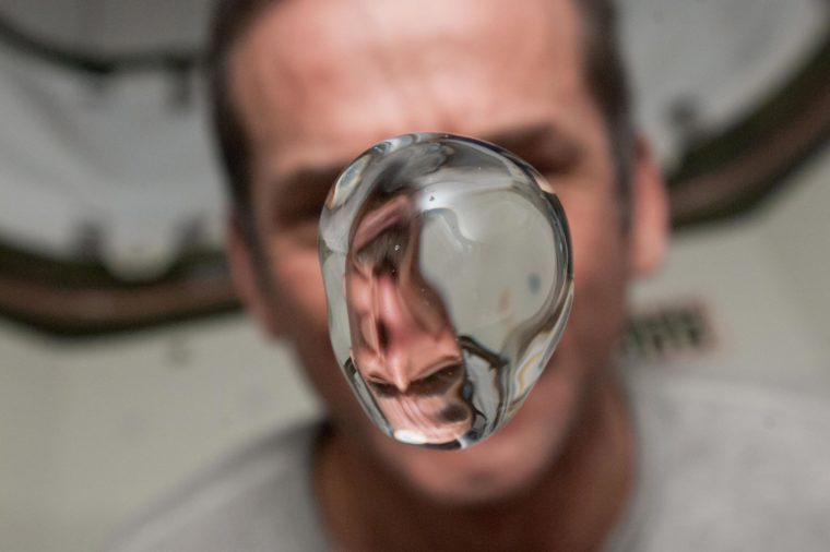 View of Canadian Space Agency (CSA) Chris Hadfield,Expedition 34 Flight Engineer (FE),watching a water bubble float freely,showing his image refracted,in the Node 1. Photo was taken during Expedition 34.