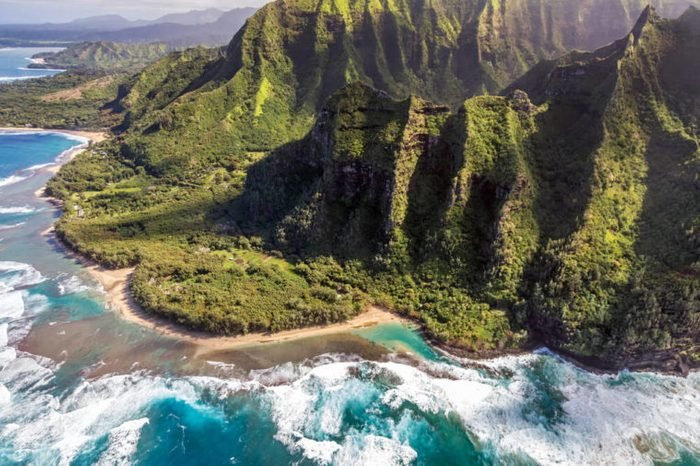 Aerial view of Kee Beach with tall, lush mountains of the Na pali coast and big waves crashing on the reef while on a doors off helicopter tour of Kauai, Hawaii.