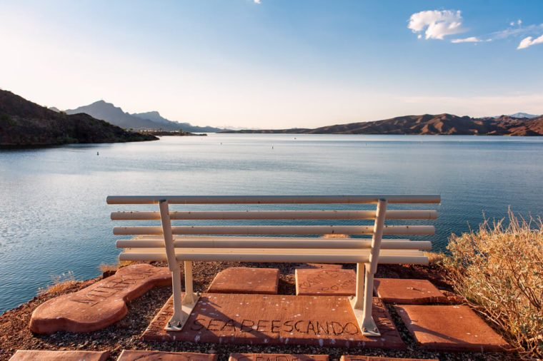 The bench in front of the lake under the blue sky