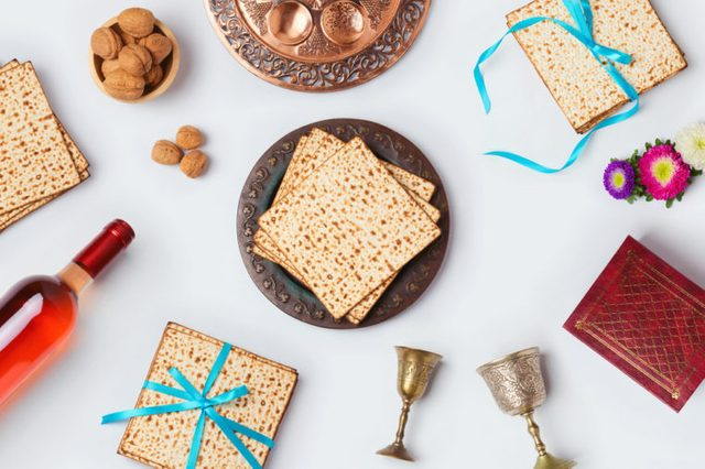 Jewish Passover holiday Pesah celebration concept with matzoh, wine and seder plate over white background. View from above. Flat lay