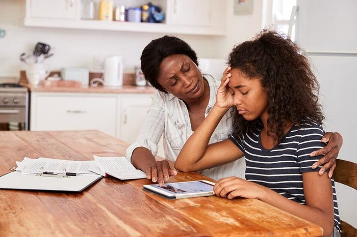 Mother Helps Stressed Teenage Daughter With Homework