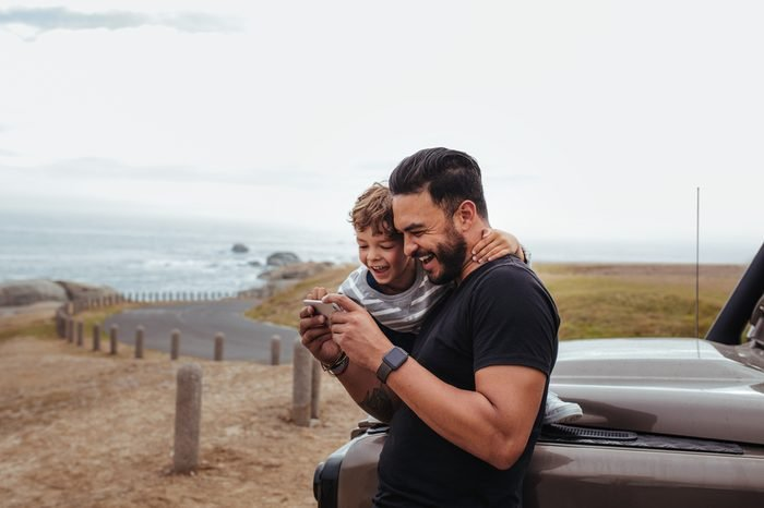 Outdoor shot of happy father and son in front of the car using mobile phone and laughing. Young man and little boy watching something on smart phone and enjoying while on road trip.