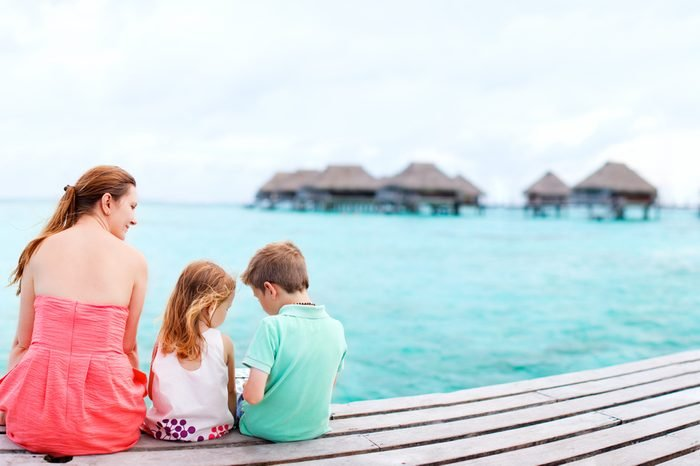 Mother and kids sitting at wooden dock enjoying ocean view