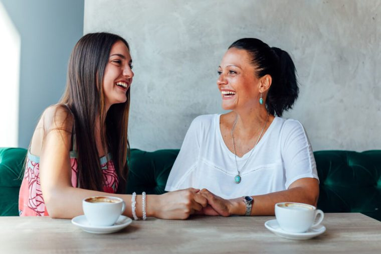 Smiling mother and daughter in a cafe