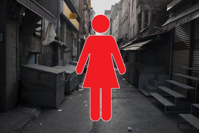 dirty, empty alleyway with woman symbol overlay