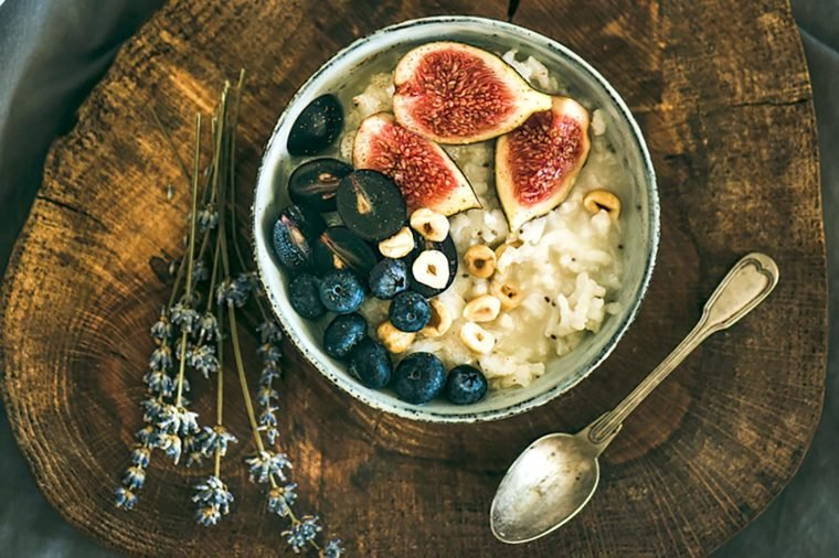 Healthy winter breakfast. Rice coconut porridge with figs, berries and hazelnuts in bowl over rustic wooden board background, top view. Clean eating, vegetarian, vegan, alkiline diet food concept