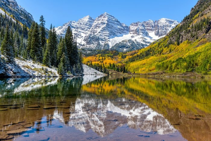 Maroon Bells and Maroon Lake - A wide-angle autumn midday view of snow coated Maroon Bells reflecting in crystal clear Maroon Lake, Aspen, Colorado, USA.