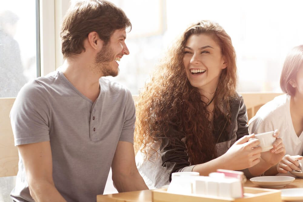Shot of two young cheerful friends talking in a cafe laughing joyfully. Beautiful young woman laughing excitedly with her male friend people relationships couple date friendship leisure lifestyle