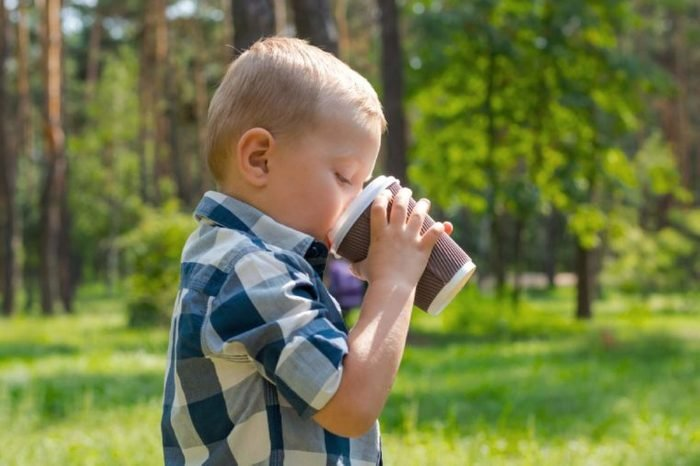 A little boy drinking from a plastic cup in the park on a sunny summer day