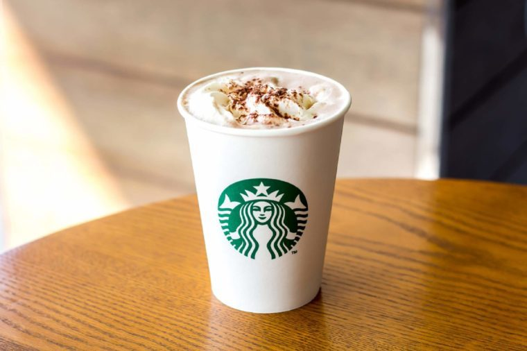 Bangkok, Thailand - December 21, 2017 : Starbucks Hot chocolate with whipping cream in white paper cup on wooden table background with copy space.