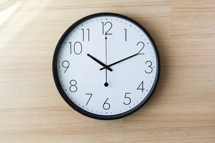 black and white clock on light wooden wall with shiny on the wall, ten past ten o'clockconcept : late appointment, late morning, wake up late,