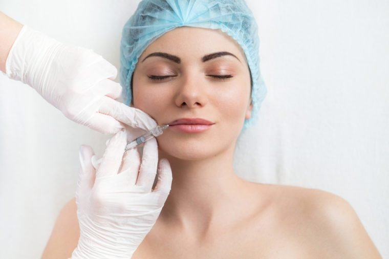 Beautiful young Woman gets cosmetic Botox injection in the face in lipps