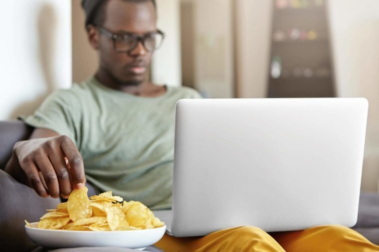Candid shot of serious concentrated single male in hat and glasses relaxing in his apartment with laptop computer and plate of chips, surfing net or watching series. Selective focus on man's hand