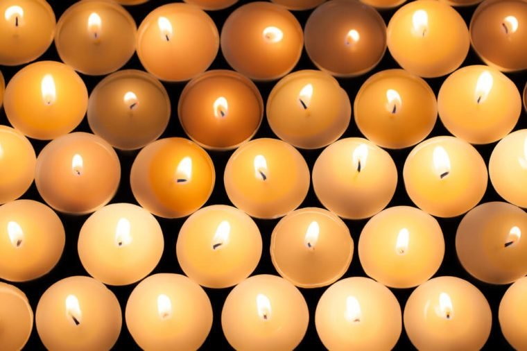 Lighted tealight candlelight background image. Lit flaming candles in rows from above. Backdrop of beautiful warm orange glow from wax candle flames.