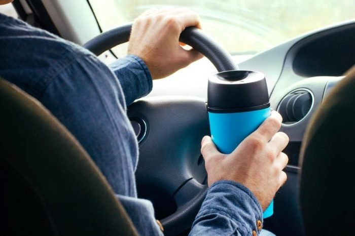 Close up of male's hand holding thermo mug with hot coffee driving in a car