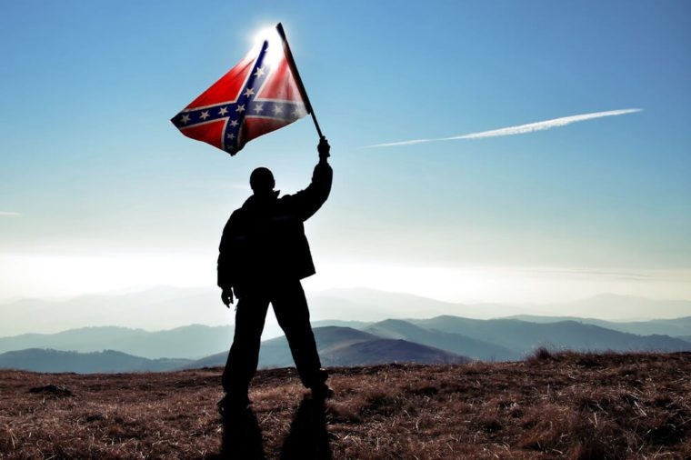 successful silhouette man winner waving Confederate flag on top of the mountain peak