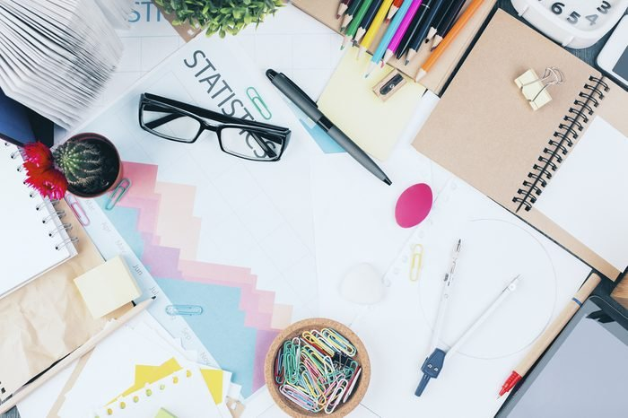 Top view of messy office workplace with business report, glasses, cactus, tablet and various stationery items