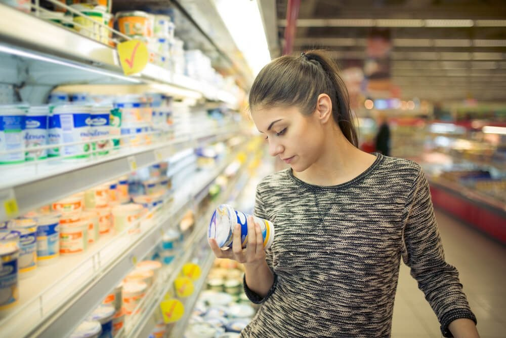 Young woman reading ingredients,declaration or expiration date on a dairy product before buying it.Curious woman reading nutritional values of the food.Shopping in the supermarket grocery store.