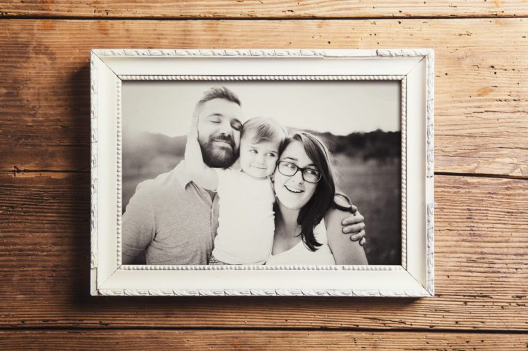 Fathers day composition - picture frame with a black and white photo. Studio shot on wooden background.