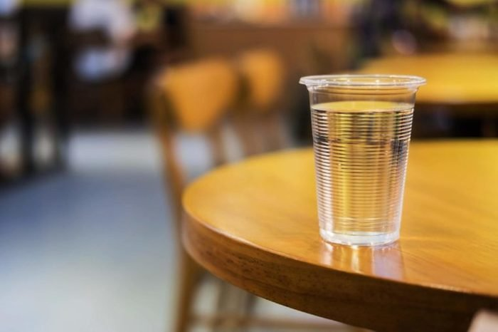 Plastic cup of water on round wooden table