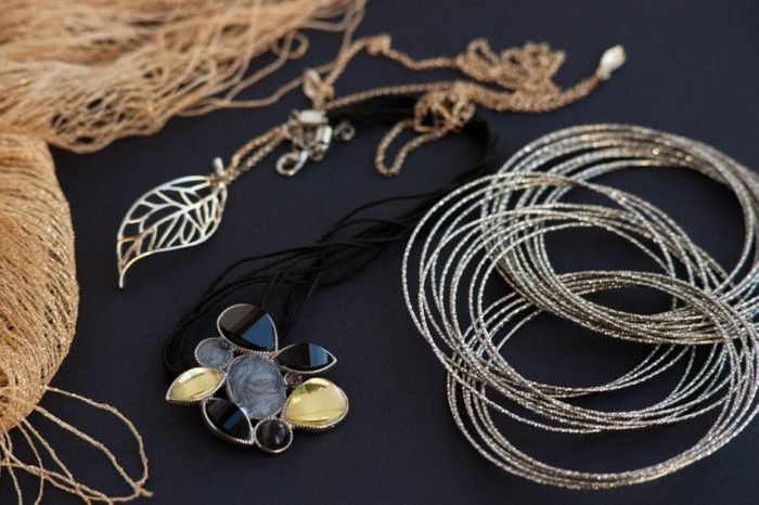 Jewelry on a black background. Golden scarf and chain on a black background. Bijouterie in golden tones on a black background looks luxurious. Silver bracelet . Style, fashion and design of jewelry.